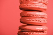 Photo close up of sweet macaroons on Living coral background. Pantone color of the year 2019 concept