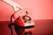 Fotografie částečný pohled ženy s životními korálové vintage rotační telefon. Pantone barva roku 2019 koncepce