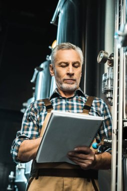 Serious senior brewer writing in notepad while examining brewery equipment stock vector
