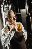 Fotografie handsome senior owner testing beer in brewery
