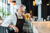 Fotografie mužské pracovník v zástěře drží pití piva v hospodě