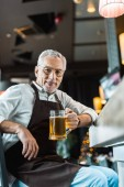 Fotografie senior worker in apron holding glass of beer near bar counter