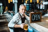 Fotografie smiling owner of pub holding open sign and glass of beer at bar counter