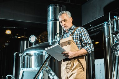 Senior male brewer in working overalls looking at notepad while examining brewery equipment stock vector