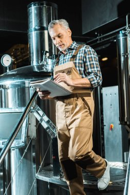 Handsome brewer in working overalls writing in notepad while examining brewery stock vector
