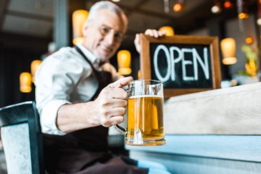Selective focus of senior owner of pub holding open sign and glass of beer stock vector