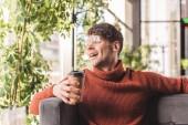 veselý muž v brýlích drží pohárek v kavárně