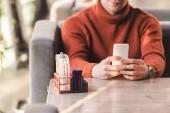 oříznutý pohled člověka pomocí smartphone u skleněných lahví se solí a papír v kavárně