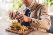 oříznutý pohled veselý mladý muž řezání chutné Burger na prkénku v kavárně