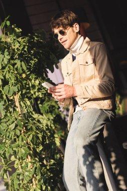 Handsome stylish man in sunglasses using smartphone stock vector