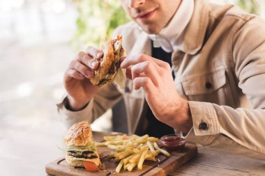 Cropped view of young man holding tasty burger near french fries on cutting board in cafe stock vector