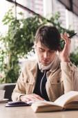 cílené muž čtení knihy a podržením pera v kavárně