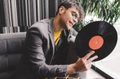 Veselý mladý muž v pohledu na vinyl záznam sluneční brýle
