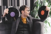 excited young man in sunglasses holding vinyl records