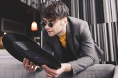 stylish young man in sunglasses looking at retro vinyl records