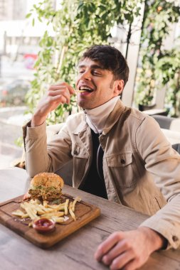 happy man eating french fry near delicious burger on cutting board in cafe
