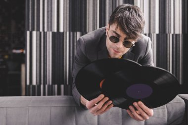 stylish young man in sunglasses holding retro vinyl records