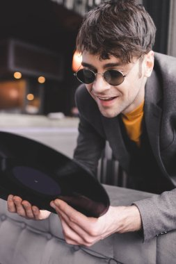 happy young man in sunglasses looking at retro vinyl record
