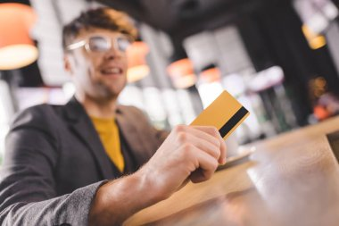 Selective focus of credit card in hand of cheerful man in glasses at bar counter stock vector