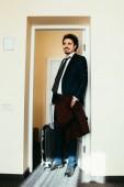 Geschäftsmann im Anzug mit Reisetasche im Hotelzimmer