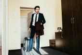 Fotografia uomo daffari in vestito con la valigia in camera dalbergo