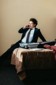 Geschäftsmann im Anzug am Smartphone sprechen, beim Sitzen auf dem Bett mit Koffer in Hotelzimmer