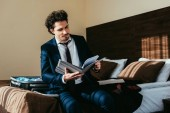 Fotografie businessman holding folder with documents in hotel room