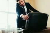 Fotografie Selektivní fokus podnikatel mluví na smartphone s kufrem na posteli v hotelovém pokoji