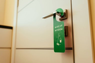 green sign with make up my room lettering on door handle, cleanup hotel service
