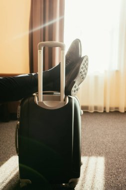 cropped view of man with legs on travel bag in hotel room