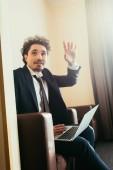 Fotografia uomo daffari che gesturing mentre si lavora al computer portatile in camera dalbergo