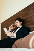 podnikatel používá smartphone a pít whiskey na posteli v hotelovém pokoji