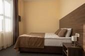 moderní hotel interiér ložnice s postelí v hnědé barvě