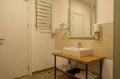 interiér koupelna s umyvadlem, ručníky, zrcadlo a vysoušeč vlasů
