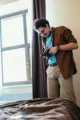 muž v brýlích, při pohledu na fotoaparát okna v hotelovém pokoji