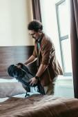 gut aussehend männlichen Touristen halten Rucksack neben Bett im Hotelzimmer