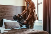 Fotografie cropped view of male tourist holding backpack near bed in hotel room