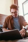 selektiven Fokus glücklicher Mann mit Laptop im Hotelzimmer mit Sonnenlicht