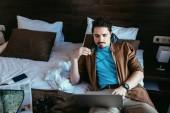Fotografie zamyšlený turistické použití přenosný počítač v hotelovém pokoji s noviny, mapy, smartphone a Fotografie fotoaparát na posteli