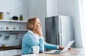zamyšlený starší žena sedí u stolu s šálkem kávy a notebooku v kuchyni