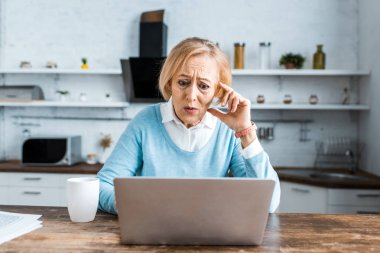 Shocked senior woman touching face, using laptop and having video chat in kitchen stock vector