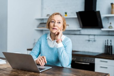 pensive senior woman sitting at table with laptop and propping chin in kitchen
