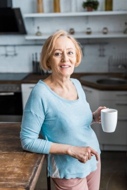 Smiling senior woman with cup of coffee looking at camera in kitchen stock vector