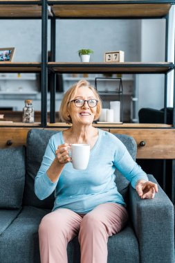 smiling senior woman in glasses sitting on couch with cup of coffee in living room