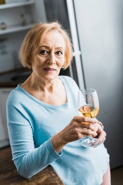 selective focus of senior woman looking at camera and holding wine glass at home