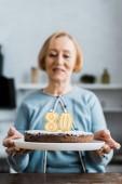 vezető nő gazdaság 80 jel torta tetején születésnapi ünnepség során