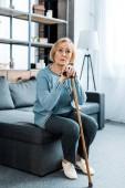 Traurige Seniorin sitzt auf Couch und hält Spazierstock zu Hause