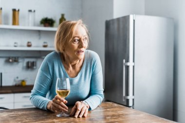 lonely senior woman holding wine glass in kitchen and looking away