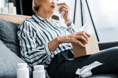 partial view of sick senior woman with runny nose holding tissue box at home