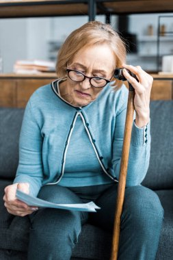 senior woman with walking stick looking at tax form at home